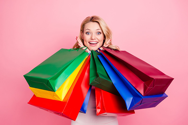 Portrait of pretty, charming, cute, excited, glad, trendy, positive, cheerful girlfriend chick covered by a lot of colorful packets with presents looking at camera isolated on pink background